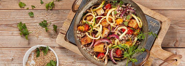Die Quinoa-Pfanne mit Zucchini-Spaghetti, Sesam und kross gebratenem Tofu aus dem REWE Rezept macht angenehm satt und ist voller bunter Zutaten. »