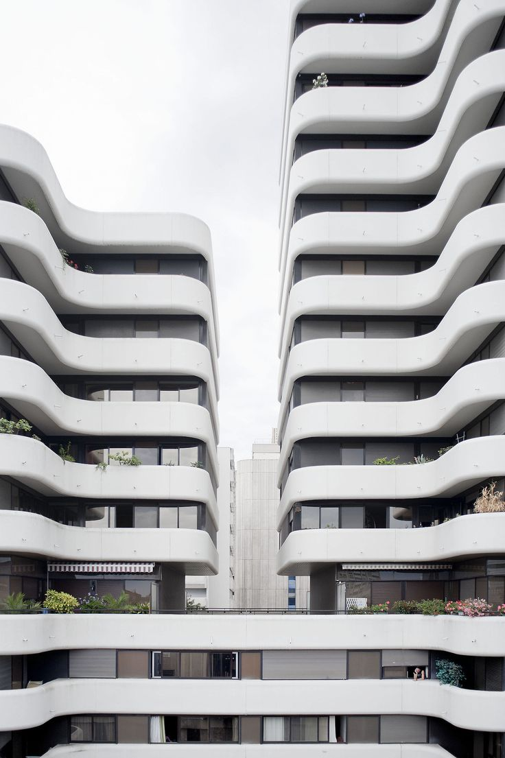 Curved high-rise apartment complex with large balconies.
