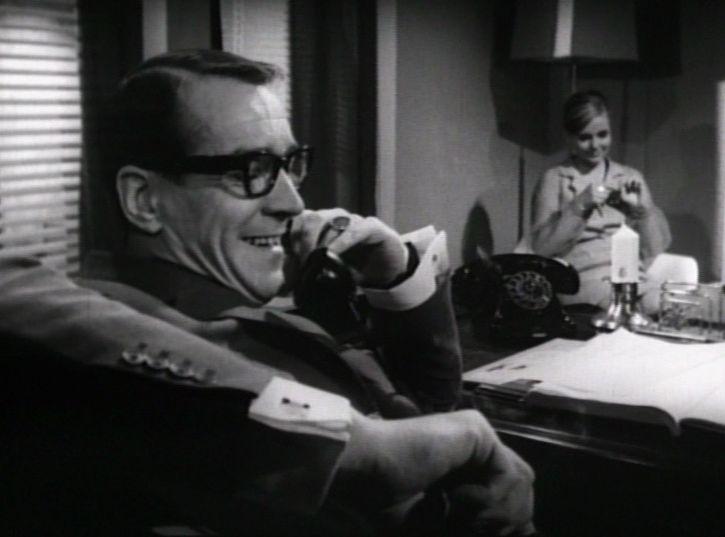 som Direktør Richard i Premiere i helvede fra 1964. Bag ved ses Joan Gamst