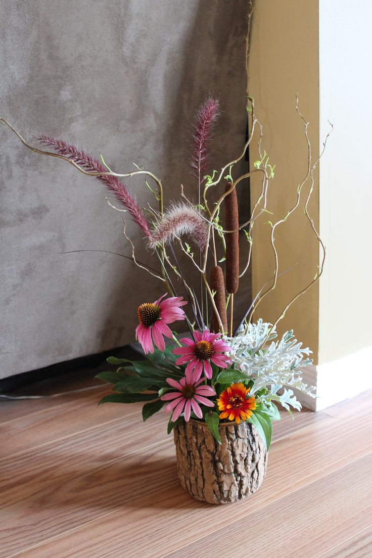 You can use flowers from the garden to make a neat arrangement in a container that mimics bark. Naturalistic design.