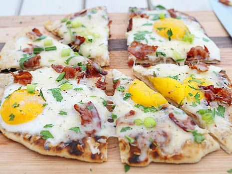 GRILLED BREAKFAST PIZZA: 12 ounces, weightPrepared Pizza Dough  Olive Oil, For Drizzling On Pizza Dough  3 wholeEggs  3 stripsCooked Bacon, Cut Up In Pieces  1 cupGrated Mozzarella  ¼ cupsGrated Parmesan  1 pinchKosher Salt  1 pinchFreshly Cracked Pepper  1 TablespoonMinced Flat-leaf Parsley  1 TablespoonMinced Chives  1 wholeScallion, Trimmed And Thinly Sliced