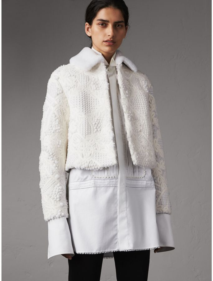 Burberry Macramé Lace-embellished Shearling Jacket by Burberry  Burberry Macramé Lace-embellished Shearling Jacket by Burberry Available Colors: White  Available Sizes: 06 00 14 08 04 02 12 10  A cropped shearling jacket intricately embellished with macramé lace that is made on traditional looms in Switzerland. The structured silhouette hints to military styles while a shearling collar contours the neck. Silky satin lines the design for a smooth fit. Wear it to add texture to a tailored…