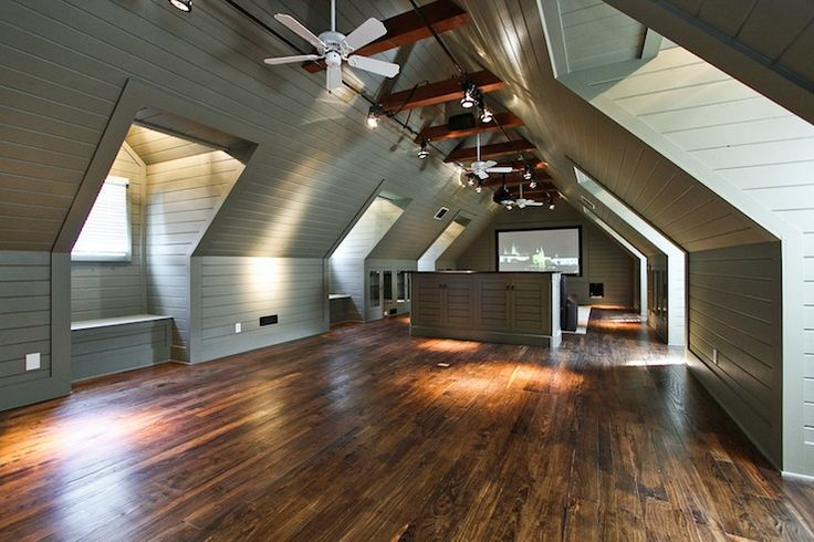 Amazing attic media room with green wood paneling and built-in TV nook.
