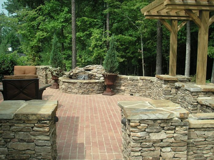 A manufactured brick patio surrounded with natural stone pillars