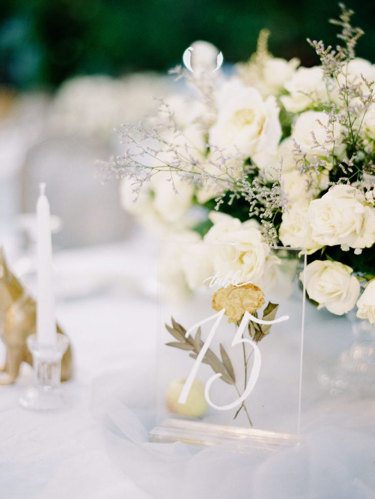 an all white tablescape with hints of gold and lucite table numbers | Photography: Angga Permana