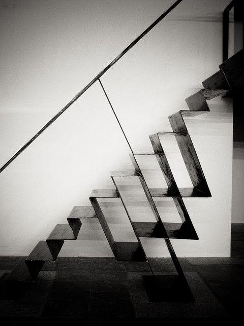 Cette escalier en tôle pliée intègre un rangement bibliothèque. Ce dernier participe à la tenue de l'escalier.