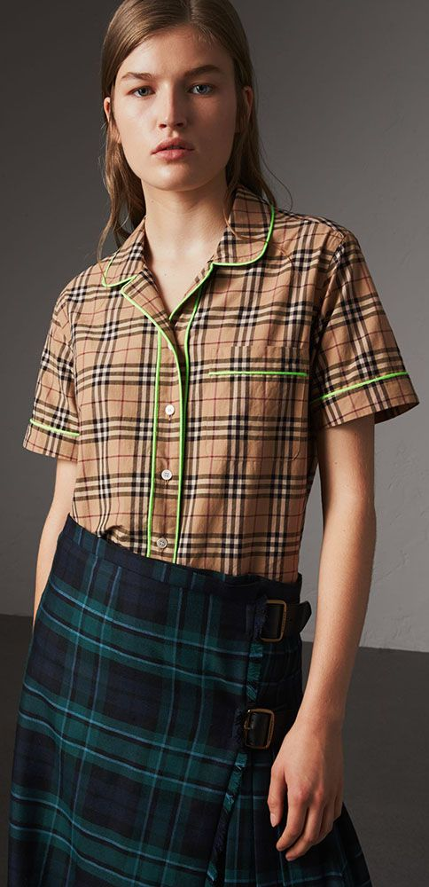 An airy cotton pyjama-style shirt by #Burberry in check, edged with vibrant neon piping. The silhouette is cut characteristically loose and features a revere collar.