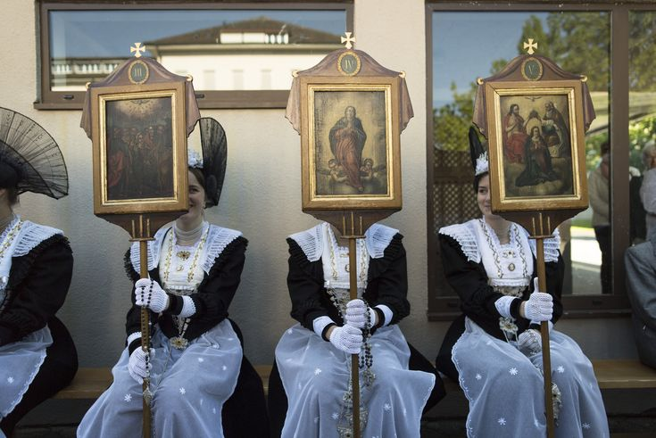 Appenzell, Switzerland Women in traditional costumes hold pictures of saints during the eucharistic celebration of the feast of Corpus Christi