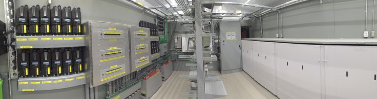 Inside the equipment room at a remote telecom site in northern Canada. The site was upgraded from being powered by propane generators to renewable energy.  An Iron Edison Lithium Iron battery is inside the cabinets on the right. On the left, 24 MidNite Classic charge controllers assist with charging.