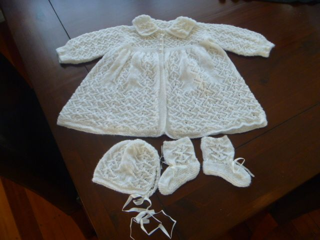 Carrying Coat with matching Bootees and Bonnet. My last baby set which was knitted for a darling wee girl.  Made from 2 ply merino with pure satin ribbon and pearl buttons.  Pattern is a zig zag lace with moss stitch and purl.  The carrying coat is knitted in one piece.  Is sized at birth to 3 months.