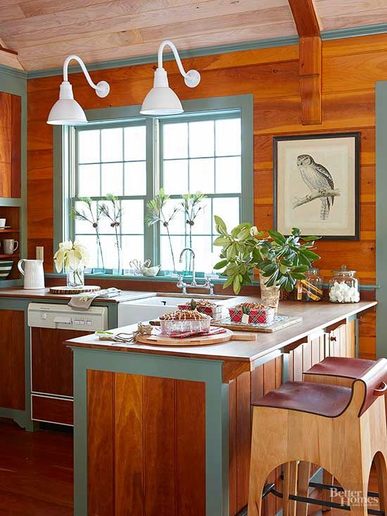 Bright white fixtures bring a sense of fun to the wood-clad wall behind this kitchen's sink. Their goose-neck forms are reminiscent of study lights, their color is cheerful, and their overall design reflects the eclectic kitchen's blend of natural and sleek surfaces with traditional design elements. /