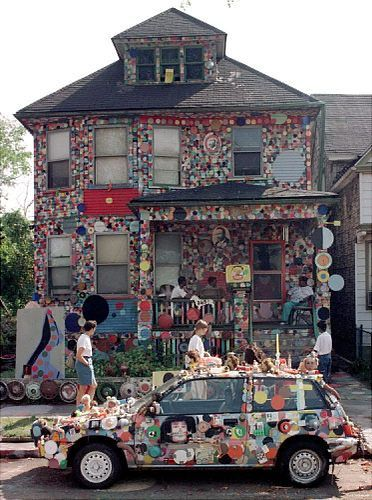 "DETROIT, UNITED STATES: Visitors walk past the``Dotty Wotty House'' 26 September, part of the Heidelberg Project in Detroit, which officials are trying to tear down. Artist Tyree Guyton creates folk art by covering part of a neighborhood with polka dots in what he calls ""art for the people and medicine for the soul."""