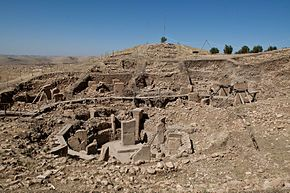 Göbekli Tepe is an archaeological site at the top of a mountain ridge in the Southeastern Anatolia Region of Turkey, approximately 12 km northeast of the city of Şanlıurfa. The tell has a height of 15 m and is about 300 m in diameter.