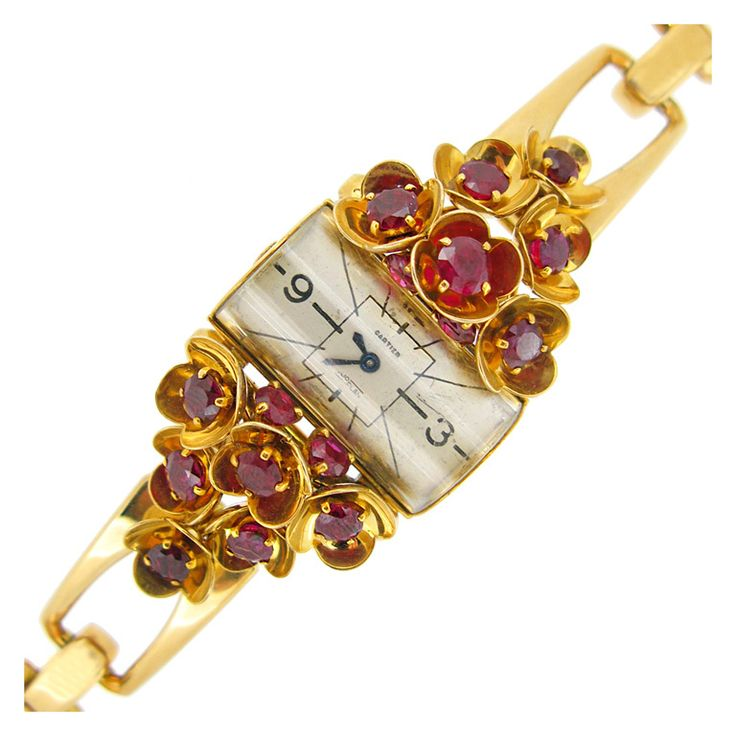 Cartier Ruby Set Watch, An extremely rare watch by Cartier, set with sixteen round old cut rubies in claw ,four flanking the central face and the remaining twelve set within protruding petal shape sculptural collets on a curving structured bezel, six to either side elegantly tapering outwards and framing the central semi-cylindrical glass watch face with black numerals, Further set with an articulated graduating rectangular link chain,18 carat yellow gold Circa 1940