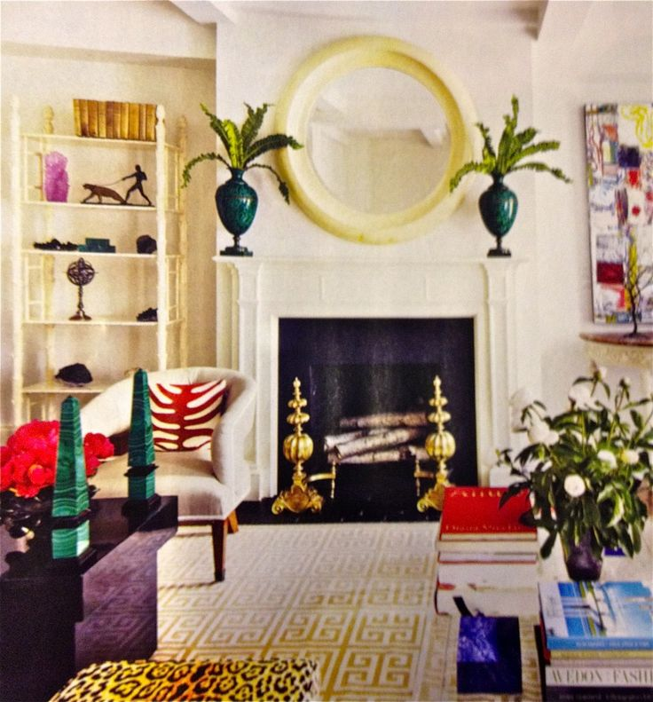 malachite urn vases and accessories, fireplace with round mirror, neutral walls with pops of color, living room