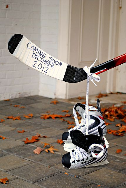 Hockey stick pregnancy announcement with hanging baby skates.