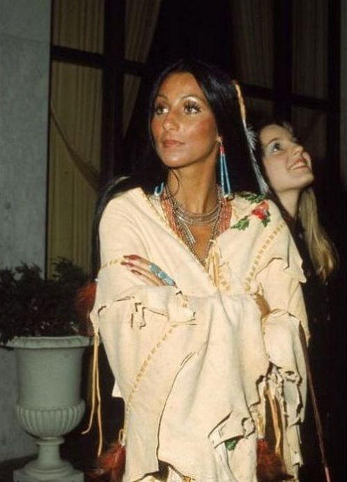 Cher wears beaded jewelry as she stands with arms folded in a Native American…