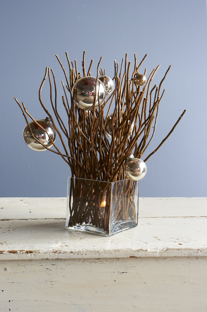 twigs and baubles in a contemporary glass cube vase with battery candle hidden inside - great Christmas table idea (lovely with twigs sprayed with white and frosted)