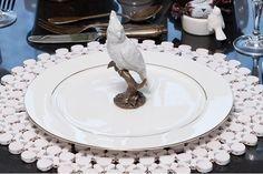 mesa posta com sousplat branco de miçangas, jogo de jantar prato com friso prata e pássaro de louça branco ao centro.