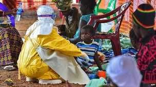 An medical worker feeds a child who is infected with the Ebola virus at a Medecins Sans Frontieres facility in Kailahun, Sierra Leone - 15 August 2014