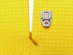 Prensatelas de Cremallera Invisible Una Cremallera Invisible, es aquella que queda oculta entre la tela, y tienen un efecto elegante en faldas, vestidos y trajes de ceremonia o de vestir. Para poder coser o sustituir este tipo de Cremalleras, necesitaremos el Prensatelas específico