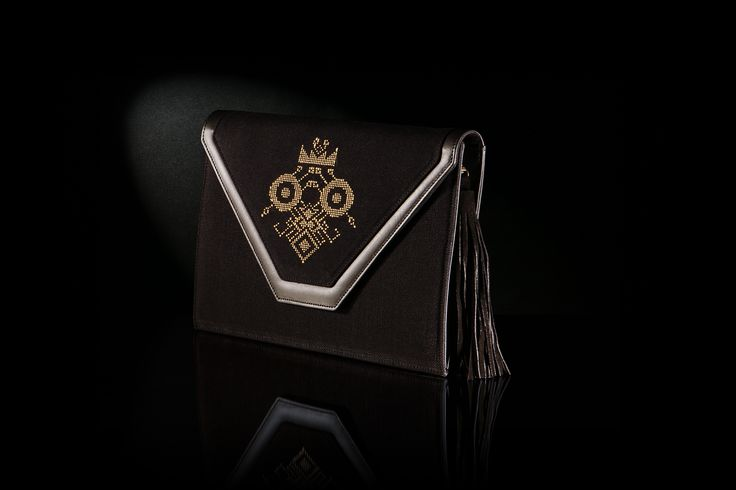 Τhe hand-woven envelope «LOOMe» is decorated with a pattern of gold silk embroidery of Byzantine style on a black background. The back of the bag has black leather lining.