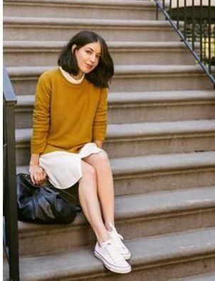 こちらは綺麗なマスタードイエローのニットセーターに白シャツとスカートを合わせたガーリーコーデ。ここにカジュアルなスニーカーを合わせることで甘すぎない着こなしに。