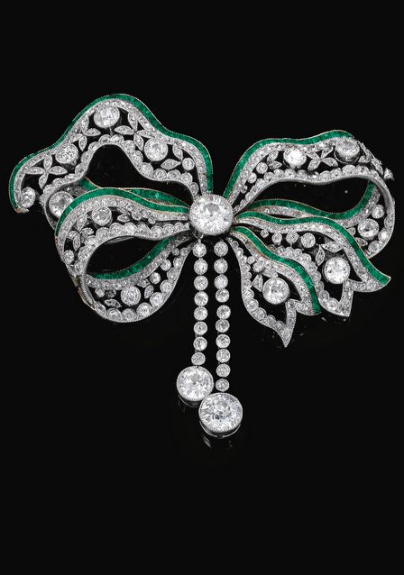 Emerald and diamond brooch circa 1900. Designed as a tied ribbon, millegrain set with circular-cut diamonds, accented with carrè cut emeralds, detachable pin to reverse.