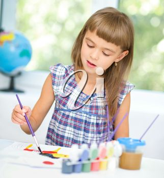 Little girl is painting with gouache while sitting at table
