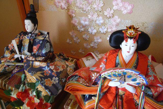 Poupées en costume de l'ère de Heian.  Cette fête remonterais à l'époque Heian.  Les jours précédant le 3 mars, les petites filles japonaises exposent de précieuses poupées posées sur des petites estrades rouges à plusieurs niveaux. Elles représentent des personnages de la cour impériale de l'ère Heian. Les poupées « hina-ningyo » étaient supposées protéger des mauvais esprits. C'est un jour de prières pour souhaiter une bonne croissance et du bonheur pour les jeunes filles du foyer.