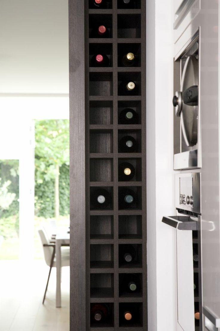 In de kopse kant van een kastenwand is dit fraaie flessenrek verwerkt. www.pieterdboer.com