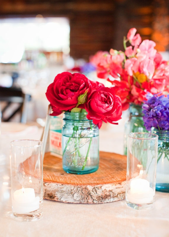 Mason jars and bright blooms on rustic wooden discs-