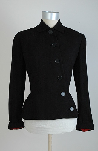 late 1940's/early 1950's Anna Miller black suit jacket with buttons that run off-center to one side. The fabric is a finely woven wool, almost a crepe. In the back there is an angled pleat with buttons running diagonally along it.