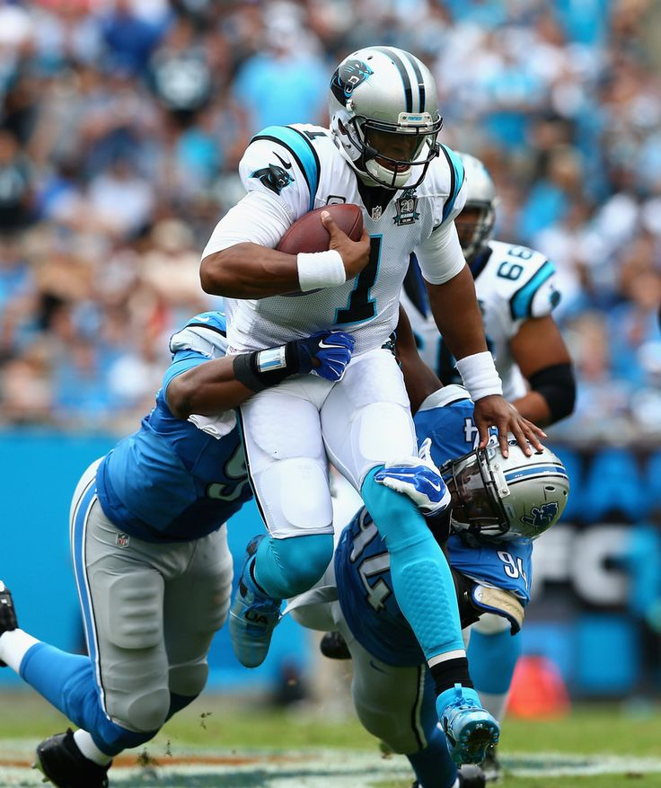 Cam Newton #1 of the Carolina Panthers runs the ball against Ezekiel Ansah #94 and Jason Jones #91 of the Detroit Lions during the game at Bank of America Stadium on September 14, 2014 in Charlotte, North Carolina.