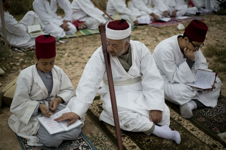 Members of the ancient Samaritan community read from a holy book during the pilgrimage for the holy day of Passover at the religion's holiest site on the top of Mount Gerizim near the West Bank town of Nablus, early Sunday, April 20, 2014. According to tradition, the Samaritans are descendants of Jews who were not deported when the Assyrians conquered Israel in the 8th century B.C.