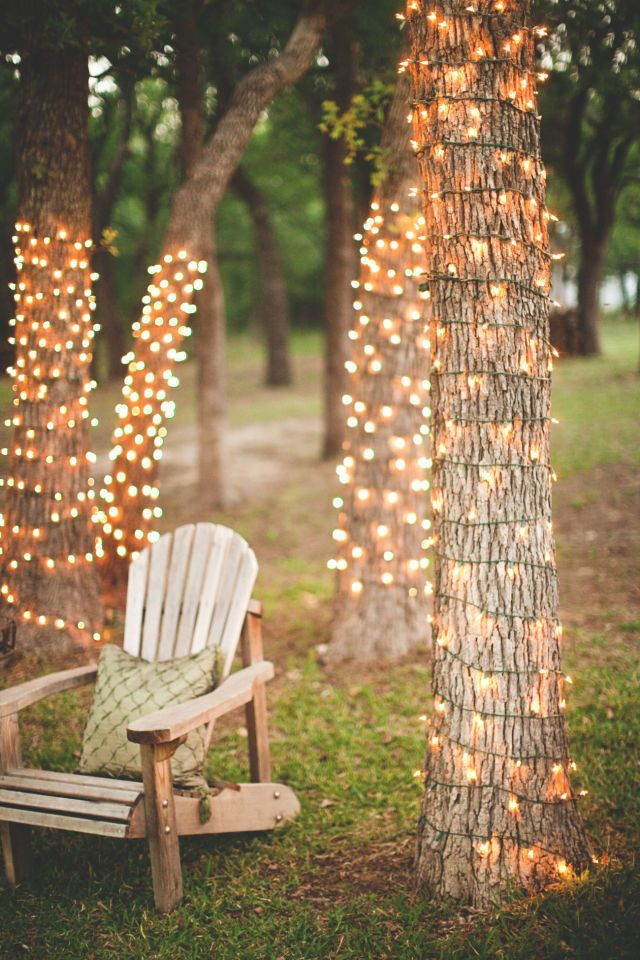Create a romantic spot by twisting a string of white lights around a cluster of trees in your backyard. Not only will this create an enchanting place to sit in the evenings, but it will be charming to look at from inside your home.  See more at Steven Michael Photography.   - CountryLiving.com