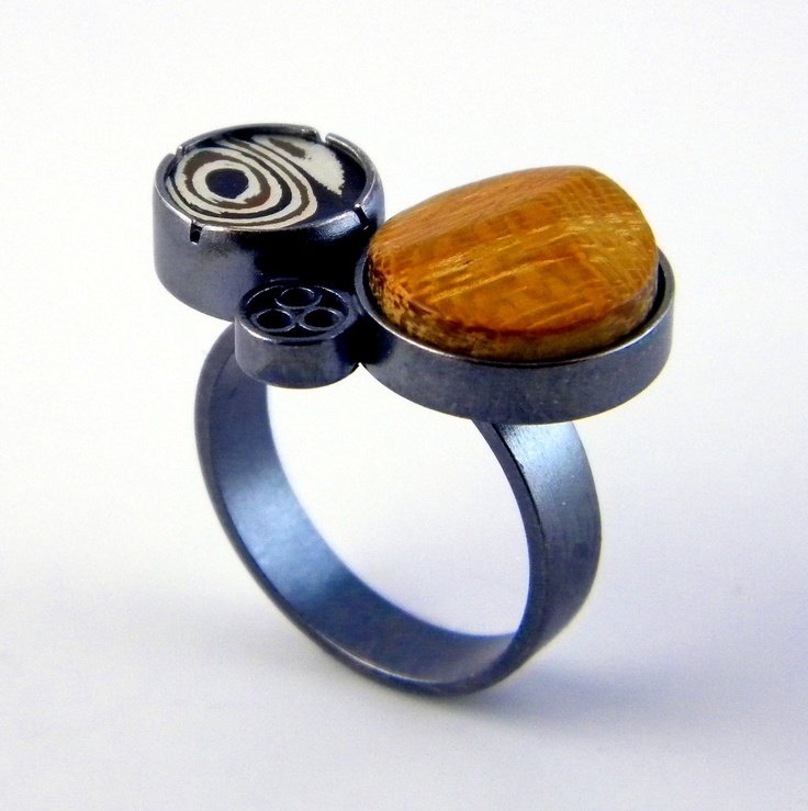 Eric Burris: ring of oxidized sterling silver accented with copper, fine silver, and shibuishi Mokume Gane and a wood cabochon.