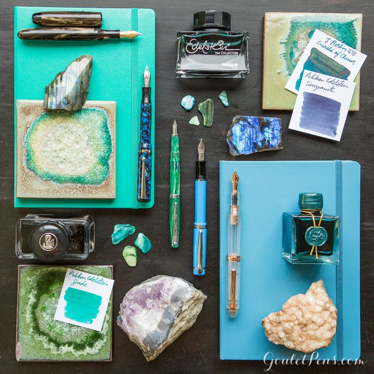 Gemstone inspired flat lay of fountain pens, ink, and notebooks.