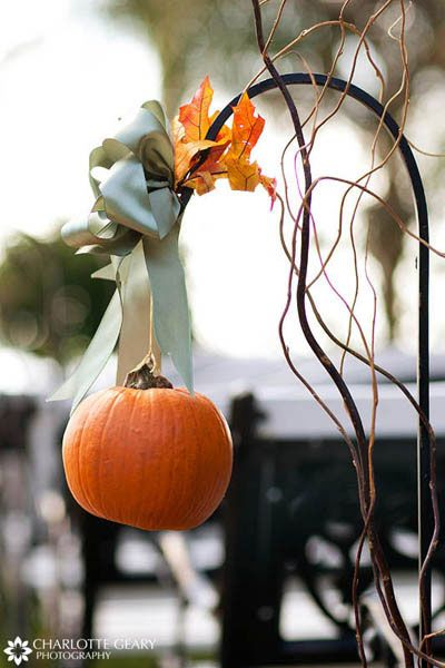 Shephards hook with ribbon and mini pumpkin for Fall yard decor.