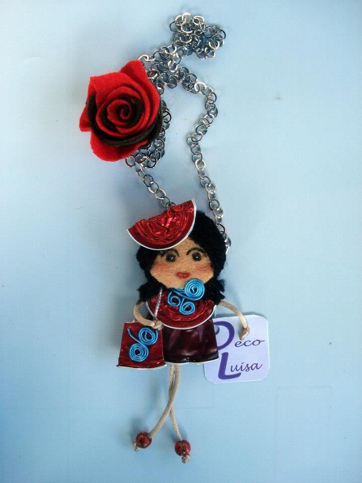 Con una rosa y bolso con adorno de aluminio en forma de espiral. Aviso estas muñecas no se pueden copiar, están registradas.