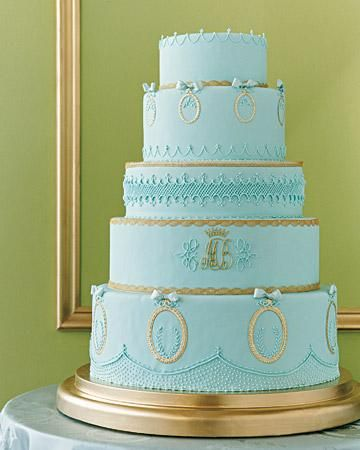 The monogram from the invitations is repeated on the blue-fondant-covered cake; it was piped in royal icing and painted with gold-luster dust. Oval rococo frames of foil-covered paper are attached to the tiers with royal icing, as are the ribbon bows. Metallic laces trim the tiers.