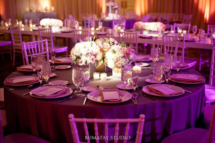 Love this #floral #centerpiece at this #peach and #purple #uplighting wedding reception! Great photo via #bumataystudio