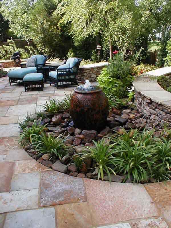 """Patio with curves and """"built in"""" landscaping areas with large rocks and grasses"""