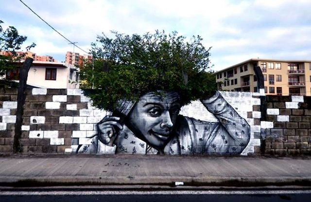 Whimsical character painted on urban wall with Green shrub hair****