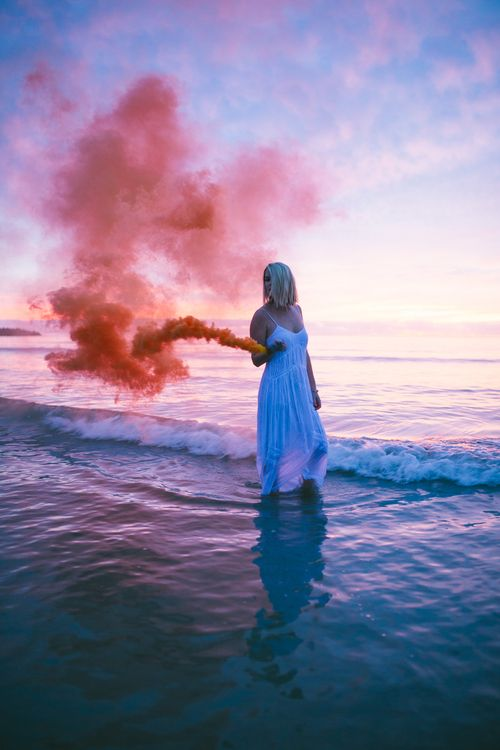 A model walking with a red smoke bomb in the ocean by sara kck photography  www.sarakckphotography.com