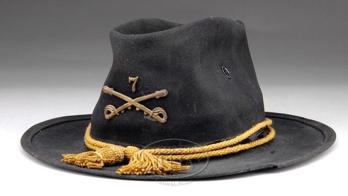ULTRA RARE 1876 PATTERN US ARMY CAMPAIGN HAT. Adopted in 1876, this black felt hat became symbolic of the Army on the western frontier and today is one of the most highly prized pcs of military headgear. It has a brim measuring approx 2-3/4″ wide with the edge turned and sewn with two rows of stitching. The crown measures approx 6″ high. There are metal vents in the left and right sides of the crown. This hat comes complete with an 1858 worsted Cav. hat cord and brass 1872 crossed sabers.
