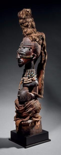 Statue Songye nkisi, République Démocratique du Congo Bois dur à patine brune et suintante par endroits, perles de verre polychromes, lamelles et cônes de métal, fibres végétales, étoffe en raphia, fourrure… - Binoche et Giquello - 22/06/2017