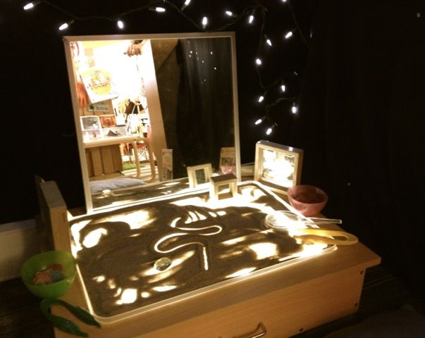 Light table with sand on top and a mirror in front - What a great way to explore all the materials around which provokes endless imagination and creativity. This reminds me of the storytelling done by using light and sand table.