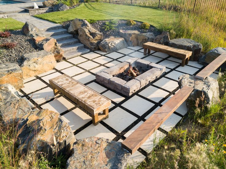 Custom firepit and offset travertine patio creates a defined space for the evening.