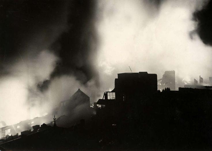 Brand. Silhouetten van de verbrande kaarsenfabriek steken af tegen de nachtelijke hemel. Er is een enorme rookontwikkeling onstaan. Gouda, Nederland, 1936. - Geheugen van Nederland